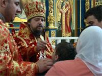 Его Преосвященство совершает Святое Таинство Причащения